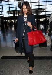 Jessica Alba carried an oversized red tote for a flight at LAX airport.