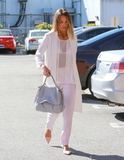 Jessica Alba headed to her office looking stylish in a white duster coat layered over a mesh-panel top.