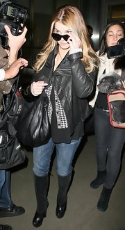 Jessica completed her black leather jacket with a pair of black leather and suede knee-high boots.