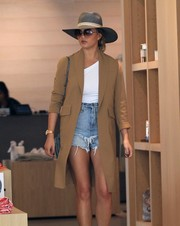 Chrissy Teigen went shopping in Beverly Hills rocking a pair of distressed jean shorts, an asymmetrical top, and a camel-colored coat.