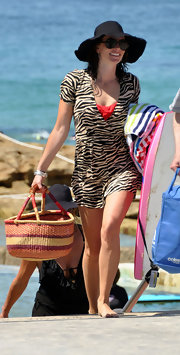 Jolene wears a black sun hat at the beach with a zebra print romper. Stylish!