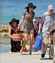 Jolene wears a leopard print romper of a red swimsuit at Bondi Beach.