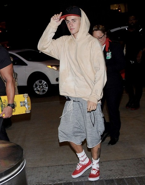 Justin Bieber completed his airport look with red canvas sneakers.
