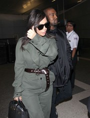 Kim Kardashian added shape to her baggy jumpsuit with a brown leather belt by Vivienne Westwood.