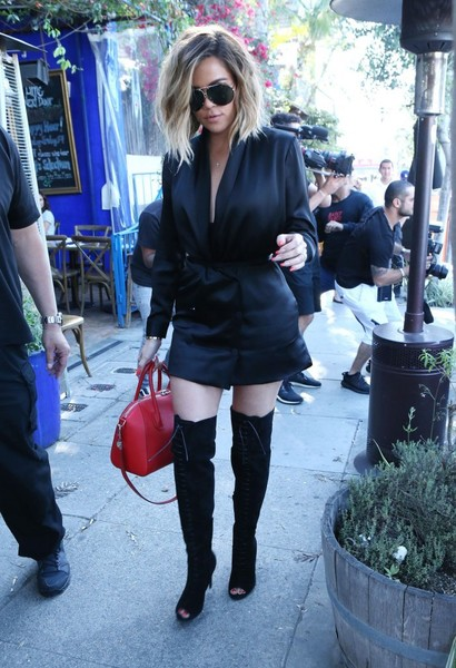 For a pop of color to her black outfit, Khloe Kardashian accessorized with a red Givenchy Antigona.