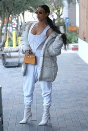 Kim Kardashian balanced out a sexy corset top with a bulky down jacket by Yeezy for a lunch out in Calabasas.