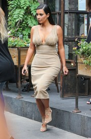 Kim Kardashian once again displayed the girls in a curve-hugging nude dress while out for  lunch in NYC.