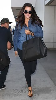 Khloe Kardashian traveled in style with this oversized black Celine bag.
