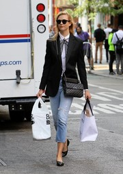 Karlie Kloss looked preppy in a BLK DNM blazer layered over a bow-print blouse while out shopping.