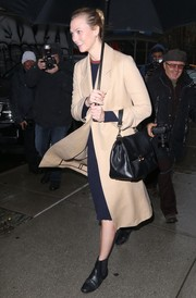 Karlie Kloss accessorized with a classic black leather tote by Carolina Herrera.