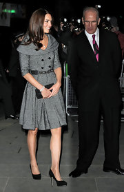 Kate Middleton topped off her look with a black clutch and matching black suede pumps.