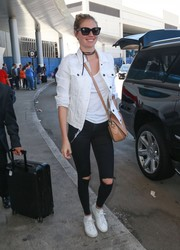 Kate Upton went for a grunge-chic airport look with a pair of ripped jeans.
