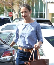 Katie Holmes accessorized with a worn camel-colored leather belt.
