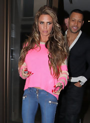 Katie Price kept to her usual Barbie style in a hot pink sweater with striped tan sleeves.