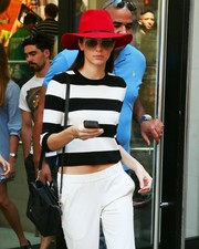 Kendall Jenner accessorized with a red Janessa Leone walker hat for a jolt of color to her monochrome outfit.