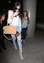 Kendall Jenner finished off her grunge-chic airport look with nude suede open-toe boots by Jimmy Choo.