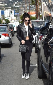 Kendall Jenner teamed a black Balenciaga leather jacket with a crop-top and leggings for a day out in West Hollywood.