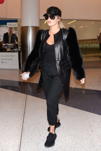 Khloe Kardashian tied her airport look together with a pair of black Yeezy 350 Boost sneakers.