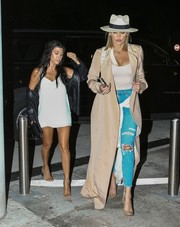 Khloe Kardashian teamed ripped jeans with a bodysuit and a long trenchcoat for a night out in Miami.