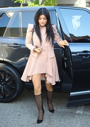 Kylie Jenner paired black cutout boots with her dress for a totally head-turning look.