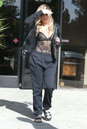 Khloe Kardashian matched her jacket with a pair of black track pants.