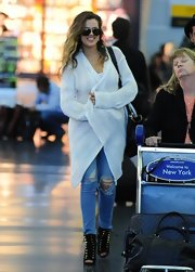 Khloe's ripped jeans added a slightly edgy touch to her travel look.