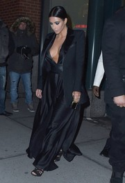 Kim Kardashian cut a provocative figure in a black Balmain silk gown with a down-to-the-navel neckline.