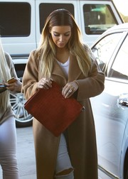Kim Kardashian went shopping in LA carrying an oversized red embossed-leather clutch by Maison Martin Margiela.