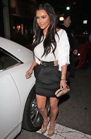 Kim Kardashian added a luxe finish to her look with a studded cream Knuckle Duster clutch with gold hardware.