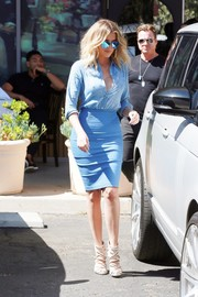 Khloe Kardashian wore her blue shirt unbuttoned halfway down for a sexier look.