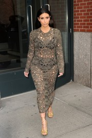 Kim Kardashian paired her dress with ultra-chic gold lace-up sandals by Tom Ford.