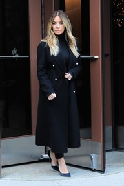 Kim Kardashian covered up in a stylish black wool coat as she left a NYC radio station.