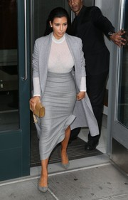 Kim Kardashian sported a semi-sheer white turtleneck and gray coat combo for a day out in NYC.