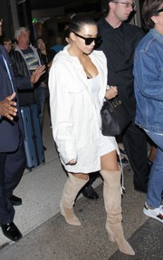 Kim Kardashian styled her white outfit with nude suede over-the-knee boots by Sergio Rossi.