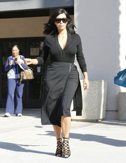 Kim Kardashian was casual-chic in a black Alaia V-neck sweater while filming her TV show.