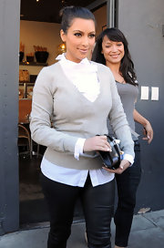 Kim wears a white button-down blouse under her v-neck sweater for her outing in West Hollywood.