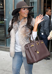 Kim K. is a big fan of the wide-brimmed hat both for summer and fall. Here she steps out in NYC in a brown felt version with a gold chain band.