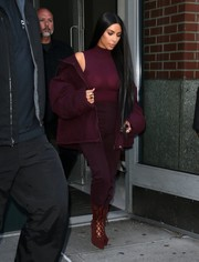 Kim Kardashian added some warmth with a padded burgundy jacket.