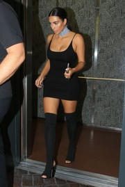 Kim Kardashian added more oomph with a pair of open-toe thigh-high boots by Yeezy.