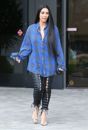 Kim Kardashian rocked an oversized plaid flannel shirt and lace-up leather pants combo while visiting a studio in LA.