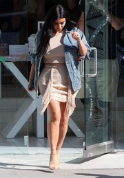 Kim Kardashian toughened up a nude crop-top with a denim jacket by R13 for a day out in West Hollywood.