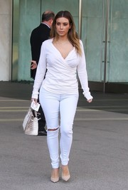 Kim Kardashian rocked a pair of ripped white skinny jeans with her stylish top.