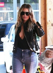 Khloe Kardashian layered a black cutout jacket over a deep-V top for a lunch out in LA.