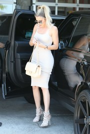 Khloe Kardashian matched a quilted nude Chanel bag with a curve-hugging dress for a visit to Milk Studios.