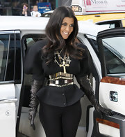 Kourtney Kardashian paired her bold blazer with layered cross necklaces, while filming scenes for her reality show. She ramped up her look with a waist cinching silver belt and elbow length gloves.
