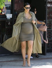 Kim Kardashian did mommy duty wearing a dark taupe maternity tank dress under a trenchcoat.