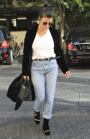 A pair of black Dries Van Noten ankle boots with metallic gold accents rounded out Kourtney Kardashian's outfit.