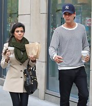 Kourtney stays cozy in an olive knit scarf while out with Scott in NY.