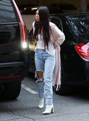 For her footwear, Kourtney Kardashian chose a pair of white ankle boots by Stuart Weitzman.