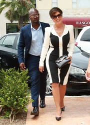 Kris Jenner polished off her look with a black crocodile clutch by Hermes.